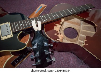 Broken guitars. Pile of smashed electric and acoustic guitar pieces. Frustrated guitarist smashed instrument parts ready for burning or repair.
