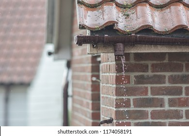 Broken gutter missing a downpipe. House guttering repair leaking rain water. Drainage problem with brown UPVC pipe.