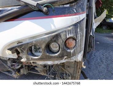 Broken headlight and front part of the bus after a traffic accident. Close-up.