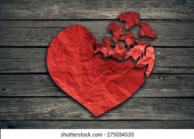 Broken heart breakup concept separation and divorce icon. Red crumpled paper shaped as a torn love on old wood symbol of medical cardiovascular health care problems due to illness