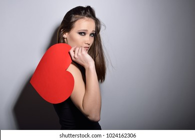 Broken heart. Heartbreaker. Beautiful girl holding large paper red heart. Temptress. Seductive woman. Portrait of young fashion woman posing at studio with red heart. Love. Valentine's day.