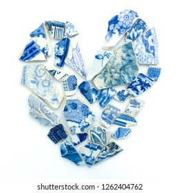 Broken heart pieces of blue white old mosaic tile fragments. Concept love hurt symbol, mend broken hearts, damaged, healing broken hearted. I love you romantic art wedding, st valentines, lovers day.