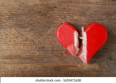 Broken heart shaped soap bar on wooden background, top view with space for text. Relationship problems concept