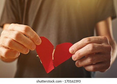 Broken hearted man. Valentines day concept. Man holding broken heart in his hands