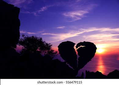 Broken heart-shaped stone on a mountain with purple sky sunset background. Silhouette Valentine background concept.