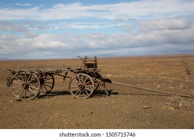 broken and historical wooden carriage dumped near the road and left to rot in the dry desert