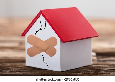 Broken House Model With Crossed Band Aid On Wooden