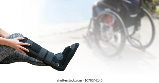 broken leg, short leg cast, splint for treatment of injured woman wearing sportswear and ankle support on blurred background patient sitting on wheelchair.