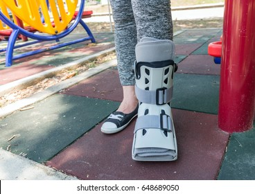 Broken leg the splint for treatment of injured woman wearing sportswear on playground background