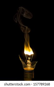 Broken light bulb burn out with flame on filament with smoke