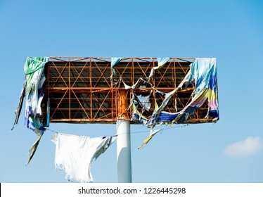Broken metal billboard in blue sky