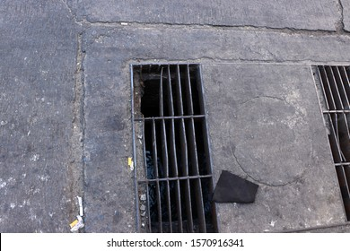 Broken metal of waterspout on the street. Danger area for walking. Damaged iron drain cover of the public sewer on the road.