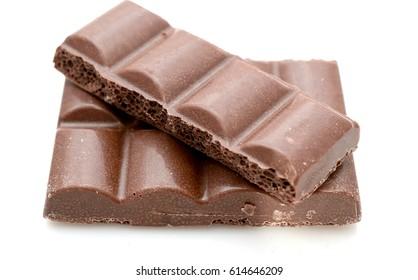 Broken milk chocolate bar isolated on white background