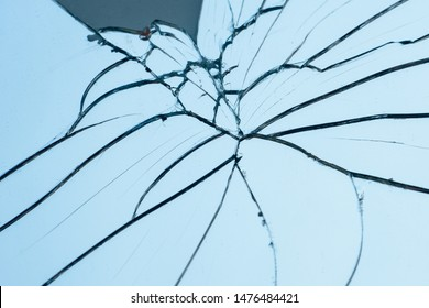 Broken mirror with fragments and cracks close-up.