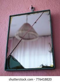 Broken mirror on pink wall