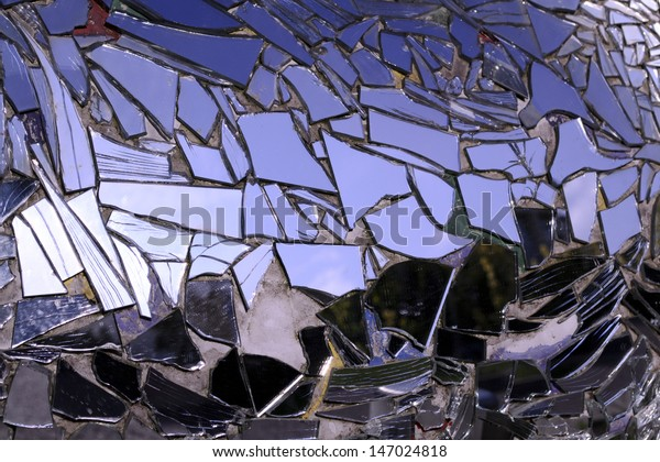 Broken  mirror and reflection on sky background
