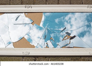 A broken mirror in a vintage white frame lies on the road, the reflection of blue sky and clouds