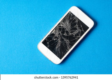 Broken mobile phone with cracked display on blue background, flat lay.