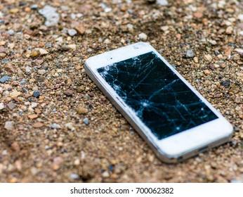 Broken mobile phone on dirt ground