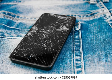 Broken Mobile Phone Screen on a Denim Background