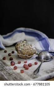 Broken muffin with wild strawberries and metal strainer on the wooden board.
