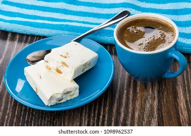 Broken nougat, spoon in saucer, blue napkin, coffee in cup on wooden table