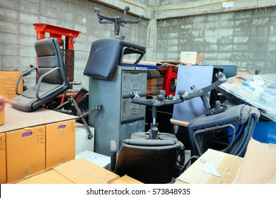 Broken office chairs and wooden cabinet in the store room