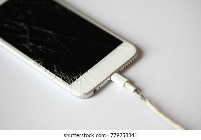 Broken old smartphone with broken display or crack screen, charge the battery with torn wire on white background