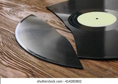 Broken old vinyl record on wooden background
