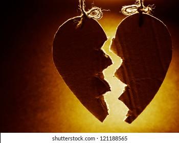 Broken paper heart hanging on rope. Front light.