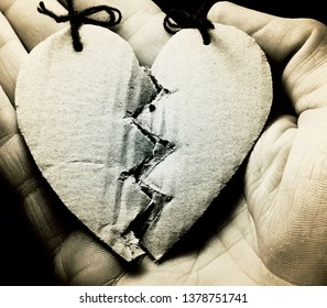 Broken paper heart on a hand. Black and white style