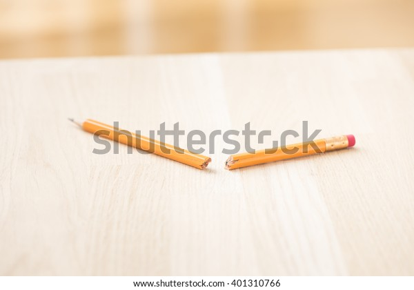 Broken pencil lying on table. Concept of frustration, writers block and school problem.