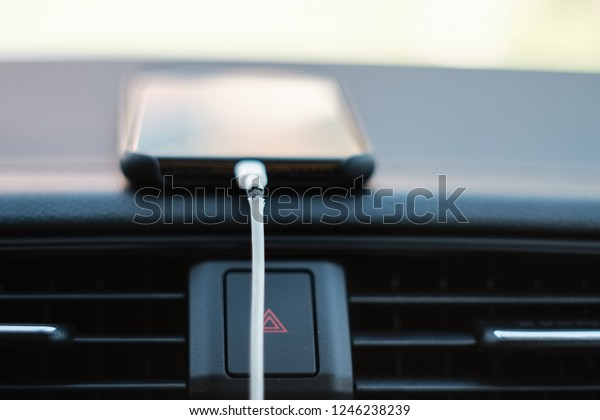 Broken Phone Charger Cable Connected to Smartphone on Car Dashboard