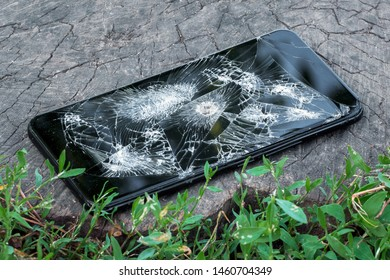 A broken phone with a hole from a bullet lies on a stump in the grass