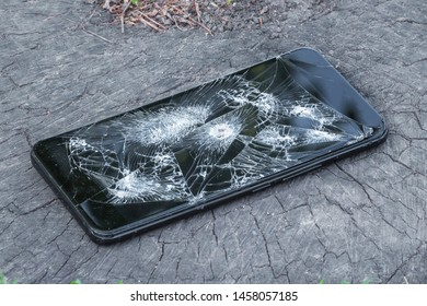 Broken phone with a hole from a bullet on a stump of thick tree