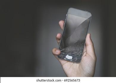 Broken phone screen in hand