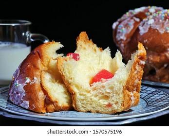Broken piece of Christmas fruit bread on plate over dark background