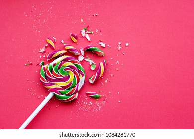 Broken in pieces candy on a stick. Smashed lollipop on pink background, top view with copy space.