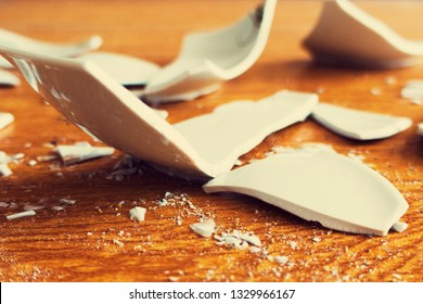 broken pieces of a cup. splinters of a broken plate. Fragments of a white ware on the floor. Metaphor of a family quarrel