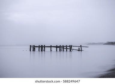 Broken pier posts in calm tranquil water, misty foggy blue background seascape