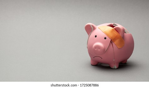 Broken piggy bank with beige adhesive on gray background.