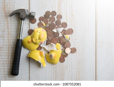 Broken piggy bank with cash and coins on wooden