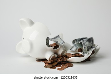 Broken piggy bank with coins and banknotes on light background