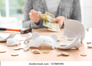 Broken piggy bank with coins and blurred woman on background