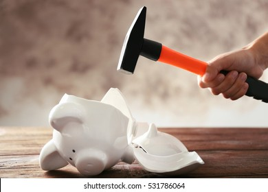 Broken piggy bank and female hand with hammer on wooden table