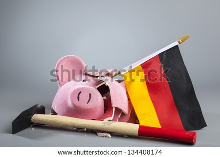 Broken piggy bank with German flag and hammer