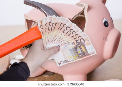 broken piggy bank with hammer and money