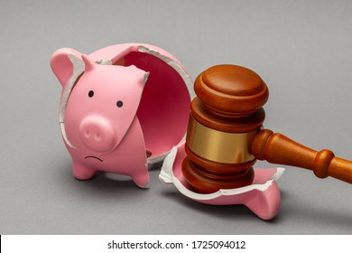 Broken piggy bank and judge gavel on gray background. Bankruptcy, crisis concept.