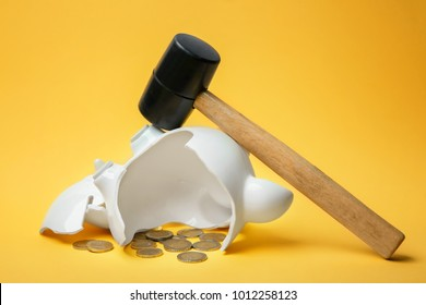 Broken piggy bank with money and hammer on color background