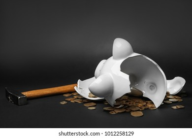 Broken piggy bank with money and hammer on black background
